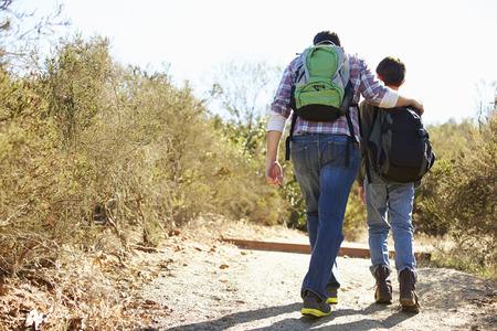 시골에서 하이킹하는 아버지와 아들의 후면보기