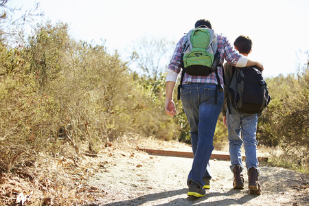Rear View Of Father And Son Hiking In Countryside photo