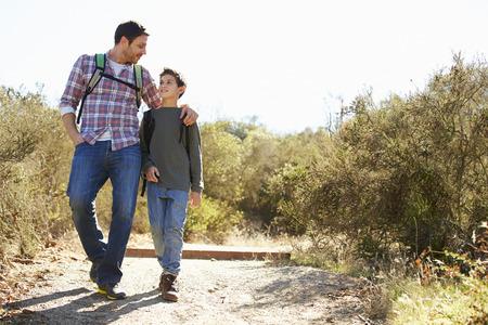 padres hablando con hijos: Padre e hijo Senderismo En Campo Usar Mochilas Foto de archivo