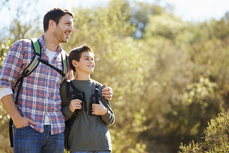 Father And Son Hiking In Countryside Wearing Backpacks Standard-Bild