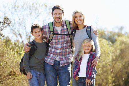 Retrato de la familia Senderismo En Campo Usar Mochilas