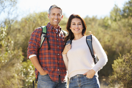Portrait Of Couple Hiking In Countryside Wearing Backpacks Imagens