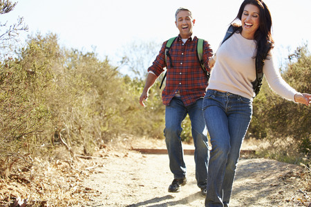 Couple Hiking In Countryside Wearing Backpacks photo