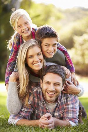 gar�on souriant: Portrait de famille couch�e sur l'herbe dans la campagne Banque d'images