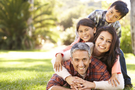 sons: Portrait Of Family Lying On Grass In Countryside Stock Photo