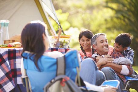 Familia que disfruta de vacaciones en camping en Campo