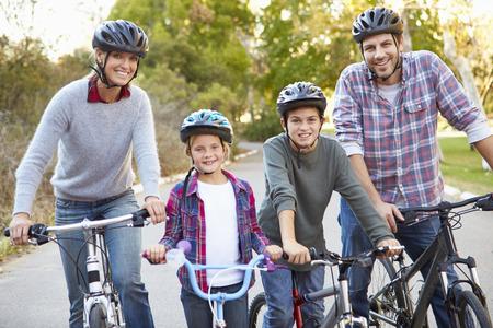 andando en bicicleta: Retrato de la familia en paseo del ciclo En Campo Foto de archivo