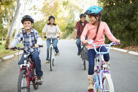Hispánský rodina na cyklu jezdit v krajině Reklamní fotografie