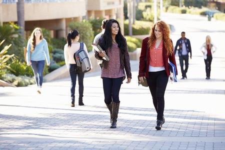 educacion universitaria: Estudiantes femeninos caminando al aire libre en el campus de la Universidad