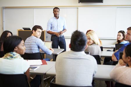 Male Tutor Teaching University Students In Classroom