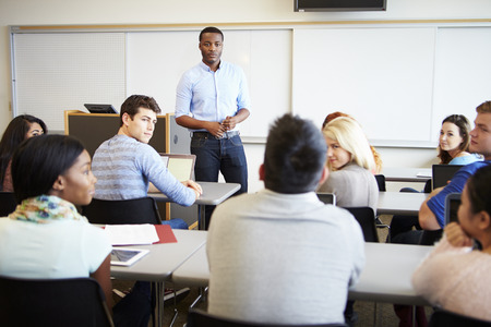 Male Tutor Teaching University Students In Classroom photo