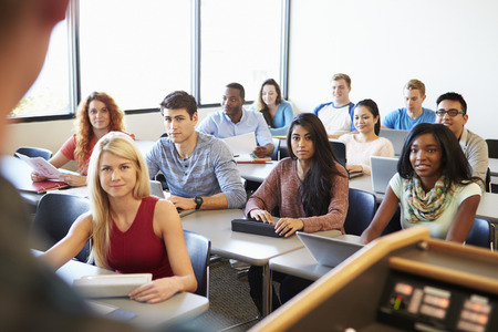 student: University Students Using Digital Tablet And Laptop In Class Stock Photo