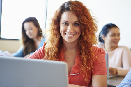 working class: Female University Student Using Laptop In Classroom Stock Photo