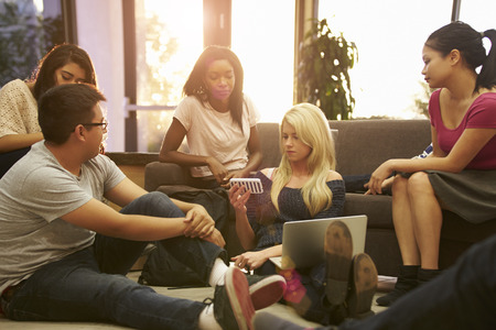 university text: Group Of University Students Relaxing In Common Room