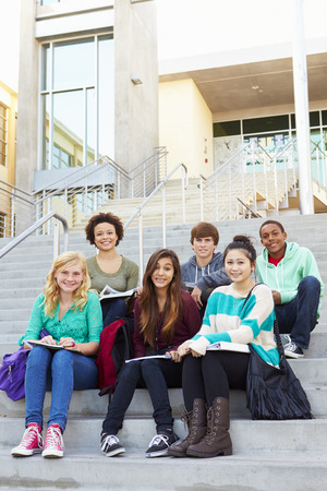 high school students: Portrait Of High School Students Sitting Outside Building