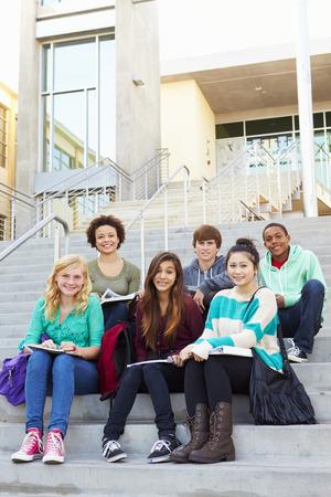 estudiantes de secundaria: Retrato de estudiantes de secundaria que se sienta fuera del edificio