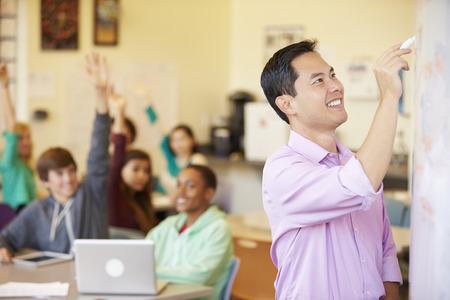 secondary school teacher: High School Students With Teacher In Class Using Laptops