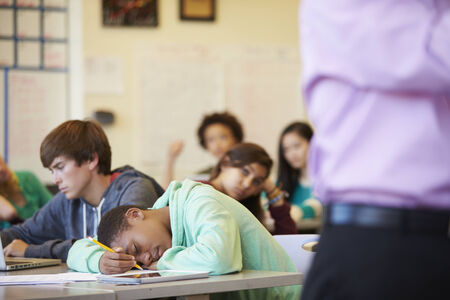 slumped: Bored High School Pupil Slumped On Desk In Classroom
