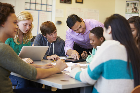 estudiantes: Estudiantes de secundaria con el profesor en clase utilizando ordenadores portátiles