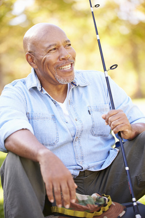Senior Man On Camping Holiday With Fishing Rod photo