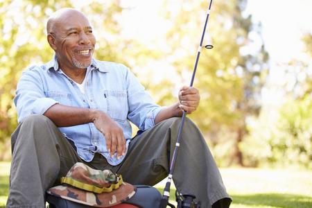 釣り竿との休日のキャンプに年配の男性 写真素材