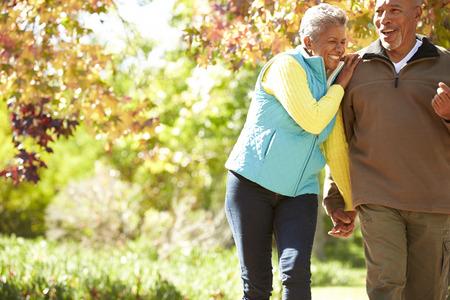 Senior Couple Walking Through Autumn Woodland photo