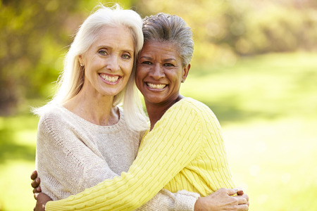 Portrait Of Two Mature Female Friends Hugging Stock Photo