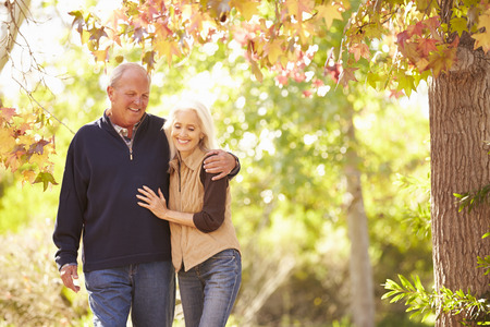 秋の森を歩く年配のカップル