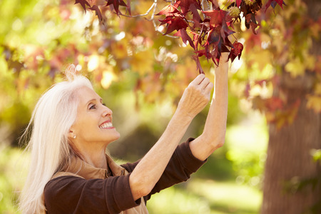 50s adult: Mature Woman Relaxing In Autumn Landscape Stock Photo