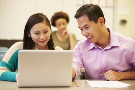 tutor: Estudiante de secundaria con el profesor en clase Usar el portátil Foto de archivo