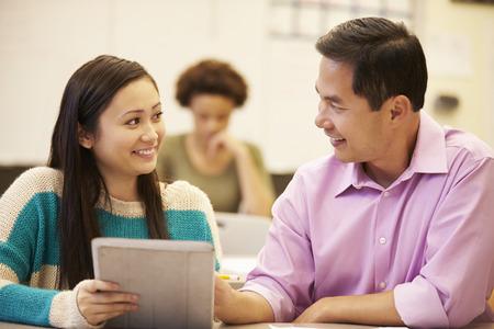high school teacher: High School Student And Teacher Using Digital Tablet Stock Photo