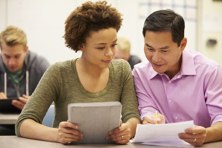 secondary school students: High School Student And Teacher Using Digital Tablet Stock Photo