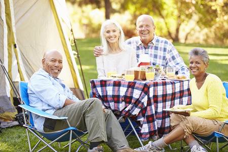 Two Senior Couples Enjoying Camping Holiday In Countryside photo