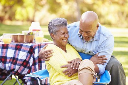 hugging couple: Senior Couple Enjoying Camping Holiday In Countryside Stock Photo
