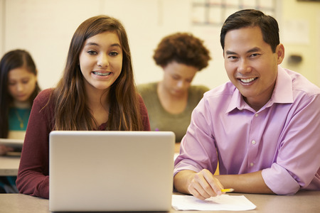 High School Student With Teacher In Class Using Laptop photo