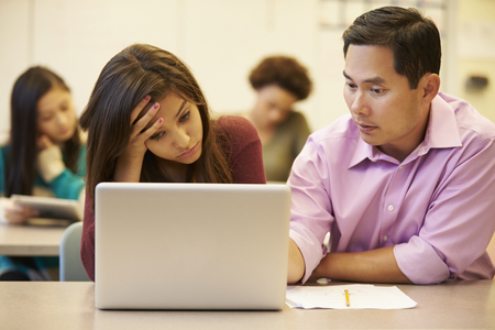 high school teacher: High School Teacher Helping Stressed Pupil In Class Stock Photo