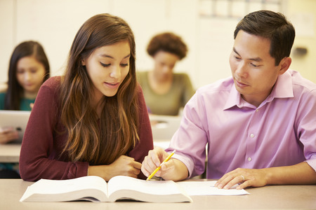 secondary education: Female High School Student With Teacher Studying At Desk Stock Photo