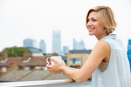 tea hot drink: Young Woman Relaxing On Roof Terrace With Cup Of Coffee Stock Photo