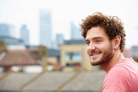 and the horizontal man: Young Man Looking Out Over City From Roof Terrace Stock Photo