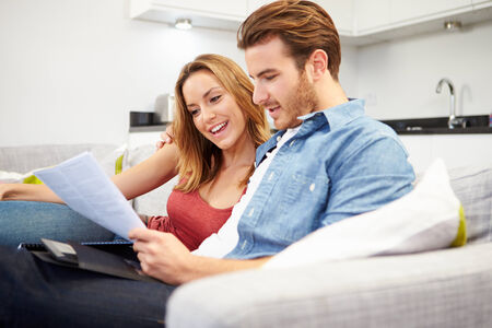 home finances: Young Couple Looking Through Personal Finances At Home