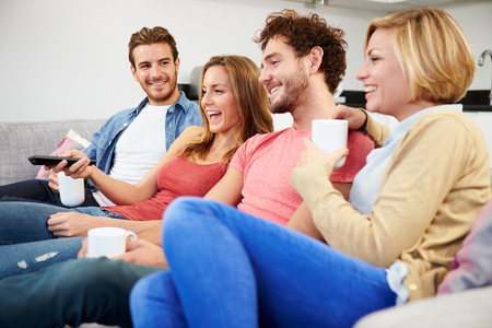 Group Of Friends Watching Television Together At Home photo