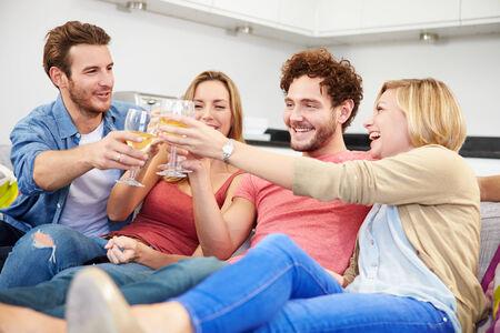 tomando vino: Grupo de amigos que disfrutan copa de vino en casa