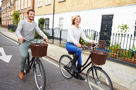 city bike: Couple Cycling Along Urban Street Together