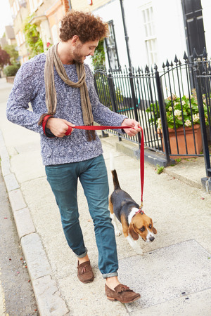 pet leashes: Man Taking Dog For Walk On City Street