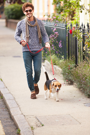 Man Taking Dog For Walk On City Street photo