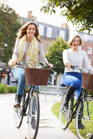 damas antiguas: Dos mujeres ciclismo a través de Parque Urbano Juntos