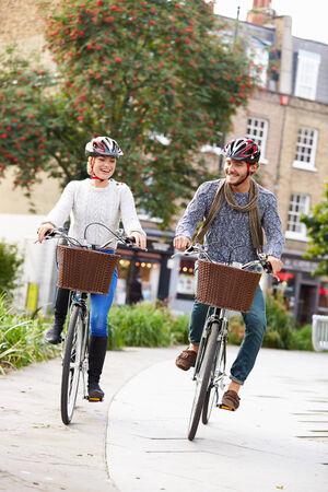 dos personas platicando: Pareja Ciclismo a trav�s de parque urbano Juntos Foto de archivo