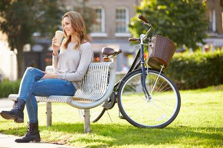 公園のベンチにテイクアウトのコーヒーでリラックスできる女性