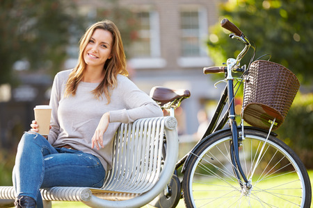 Woman Relaxing On Park Bench With Takeaway Coffee Banque d'images