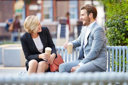커피와 함께 공원 벤치에 비즈니스 커플 스톡 콘텐츠